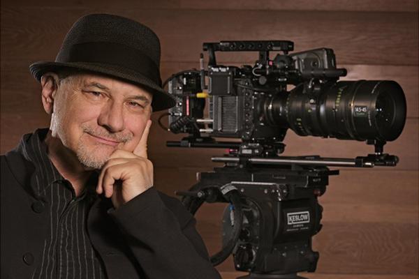[photo] Newton Thomas Siegel posing infront of a cinema camera with a Fujinon lens