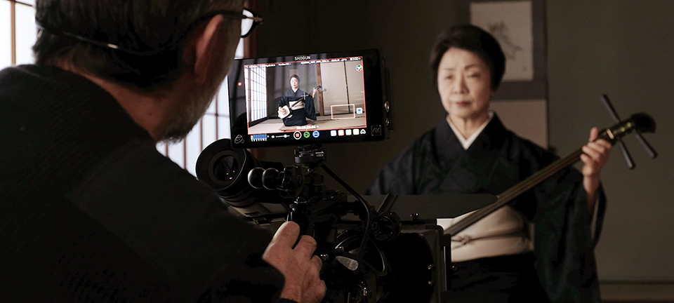 [photo] A cameraman looking through an external monitor while shooting a Japanese lady subject playing a Japanese Guitar Shamisen