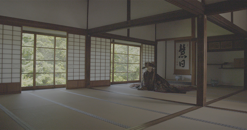 [photo] A less saturated photo of a lady dressed in a Japanese attire sitting on the floor Japanese temple