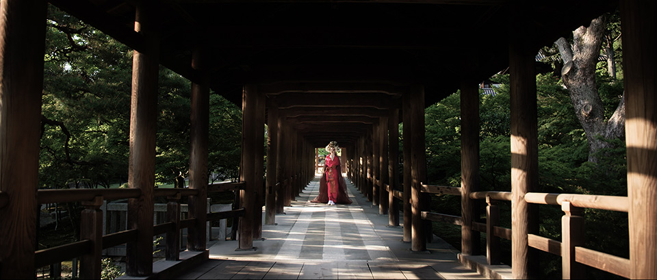 [photo] A color saturated version of a lady in traditional Japenese attire standing under a wooden bridge