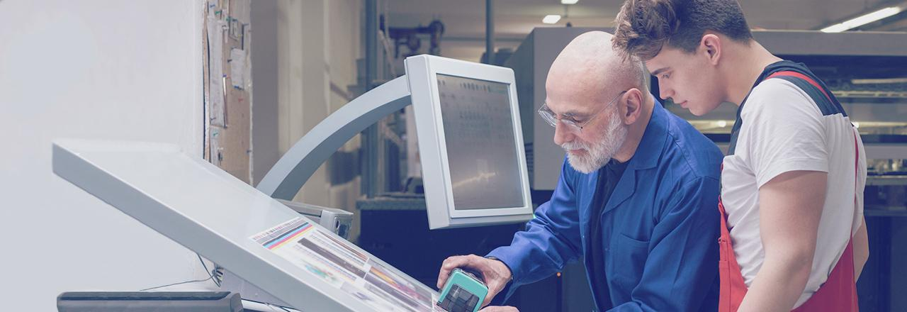 [photo] Older man with beard and glasses and young man looking at printouts on elevated flatbed of machine