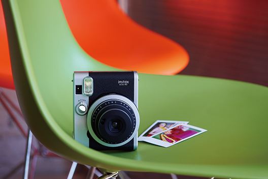 Black mini 90 camera with two photos on green chair