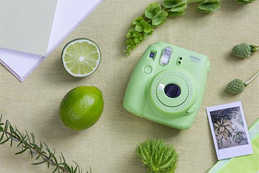 Imagem de uma câmera Mini 9 verde lima sobre uma mesa com outros itens na cor verde