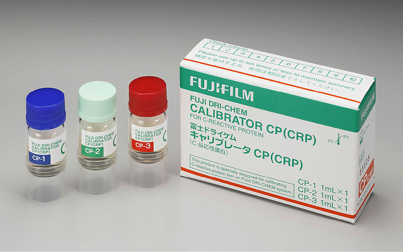 [foto] Três frascos de calibrador CP (CRP) - CP-1 com tampa azul, CP-2 com tampa verde clara e CP-3 com tampa vermelha, ao lado da caixa do calibrador CP (CRP)