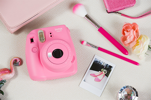 Image of Flamingo Pink Mini 9 camera on the table with other items in similar color