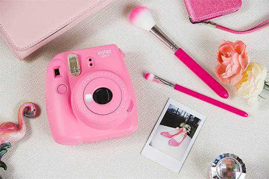 Imagem de uma câmera Mini 9 rosa flamingo sobre uma mesa com outros itens com cores similares