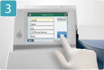 [foto] Mão com luva pressionando o botão START (Iniciar) na tela sensível ao toque do DRI-CHEM NX500V
