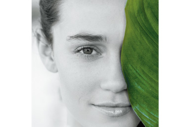 Imagem de uma mulher atrás de uma grande folha verde com filtro Verde Parcial aplicado onde tudo, exceto a folha, é preto e branco