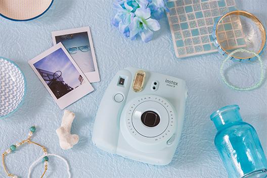 Imagem de uma câmera Mini 9 azul aqua sobre uma mesa com outros itens