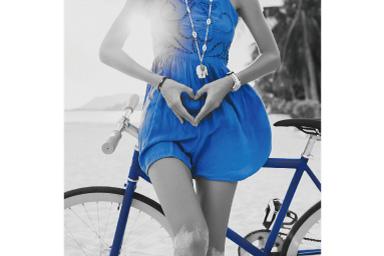 Imagem de uma mulher com vestido azul, de pé diante de uma bicicleta com filtro azul parcial aplicado onde tudo, exceto o vestido, é preto e branco