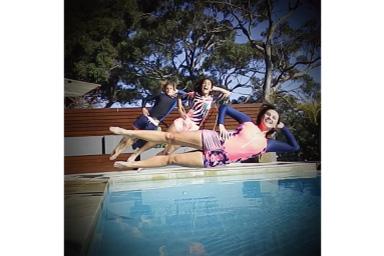 Imagem de três pessoas pulando na piscina com vinheta preta