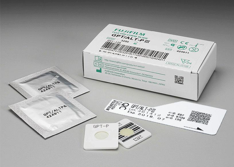 [foto] Caixa de lâminas GPT/ALT-PⅢ DRI-CHEM com duas lâminas enroladas em papel alumínio, duas lâminas sem embalagem (vista frontal e traseira) e cartão QC