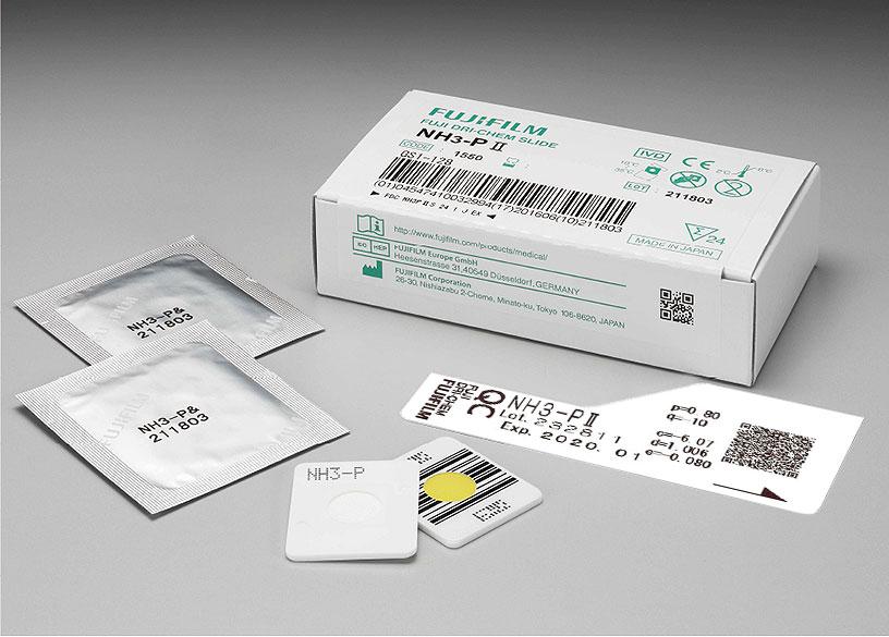 [foto] Caixa de lâminas NH3-PⅡ DRI-CHEM com duas lâminas enroladas em papel alumínio, duas lâminas sem embalagem (vista frontal e traseira) e cartão QC