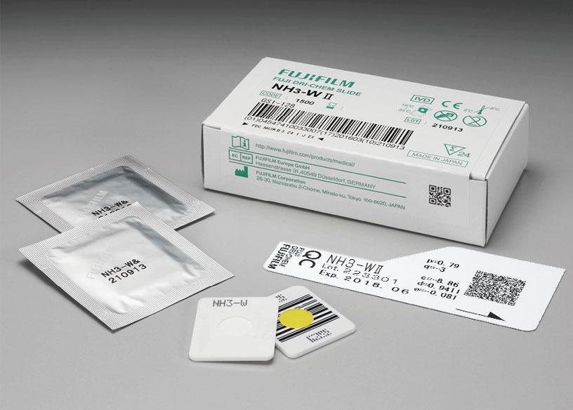 [foto] Caixa de lâminas NH3-WⅡ DRI-CHEM com duas lâminas enroladas em papel alumínio, duas lâminas sem embalagem (vista frontal e traseira) e cartão QC