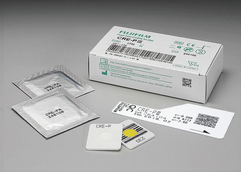 [foto] Caixa de lâminas CRE-PⅢ DRI-CHEM com duas lâminas enroladas em papel alumínio, duas lâminas sem embalagem (vista frontal e traseira) e cartão QC