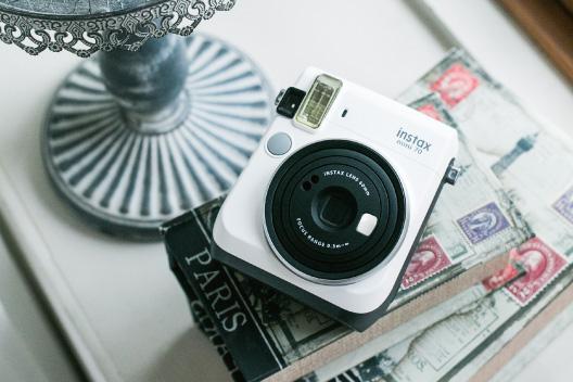 Uma câmera mini 70 branca em cima do livro na mesa de apoio