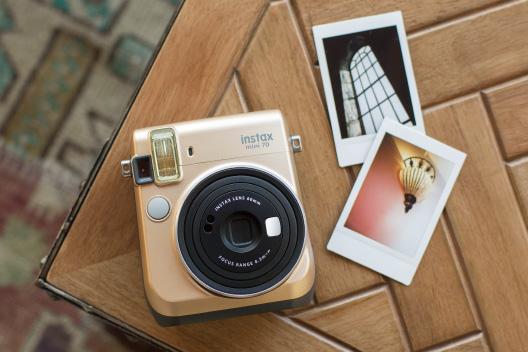 Câmera mini 70 dourada na mesa de madeira com duas fotos