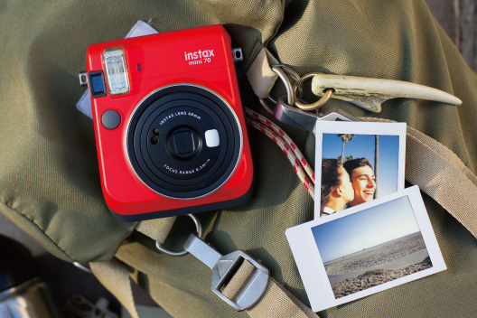 Câmera mini 70 vermelha com duas fotos sobre bolsa verde.