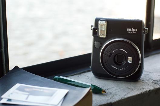 Câmera mini 70 meia-noite escura ao lado da janela com caneta e caderno