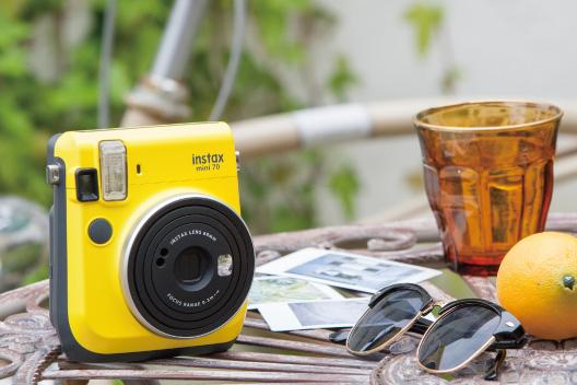 Câmera mini 70 amarelo claro na mesa com óculos de sol, limão e copo