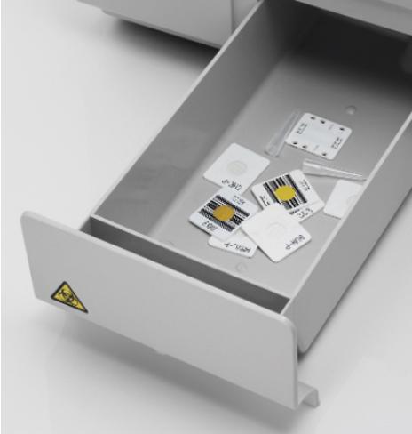 [foto] Caixa de descarte aberta com lâminas descartadas dentro da bandeja; caixa rotulada com adesivo de risco biológico amarelo no canto