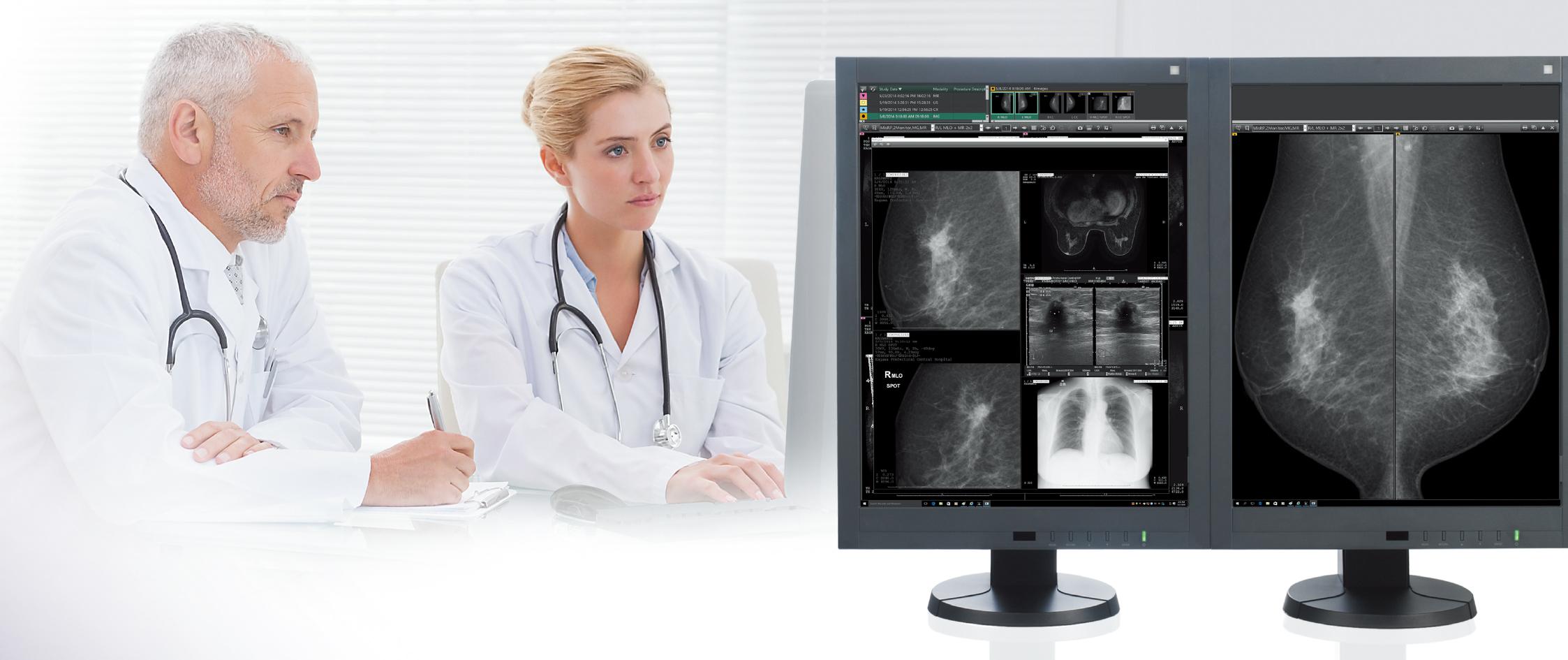 [foto] Um homem e uma mulher vestidos com jalecos de laboratório olhando para várias imagens de mamografia em uma tela de computador