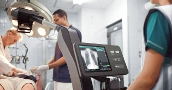 [photo] Person standing in front of FDR Nano interface with x-ray image of chest on screen