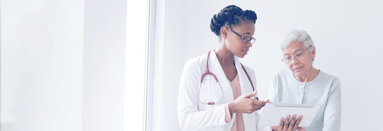 [foto] Médica com jaleco branco mostrando a tela do tablet para paciente idoso
