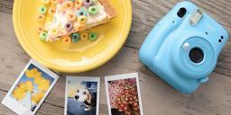 [photo] Instax camera in blue with a yellow plate with cake and cereal and 3 sample photo print outs