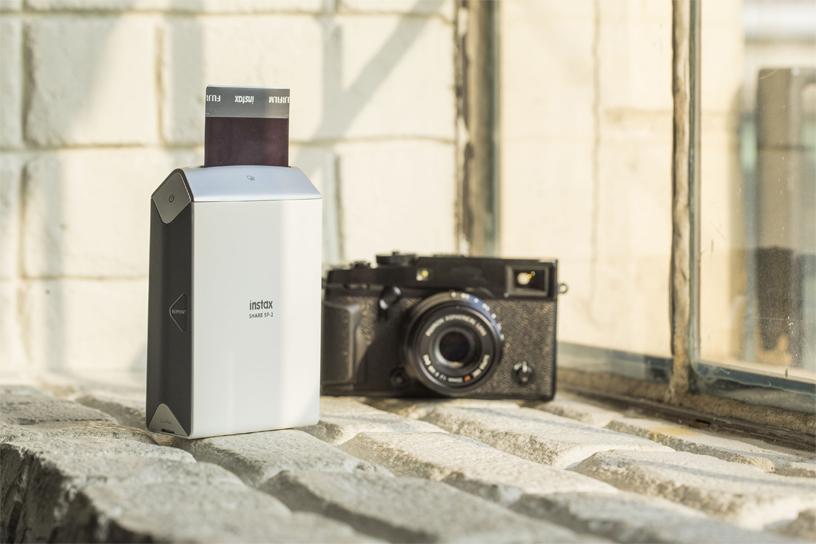 Imprimante SP-2argent à côté de l'appareil photo noir près de la fenêtre