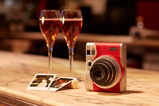 [photo] Instax mini 90 in silver and red on a wooden counter top with 2 glasses of wine and photo print outs laying over a cork