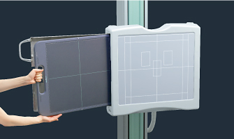 [photo] Hands loading a panel into X-ray stand