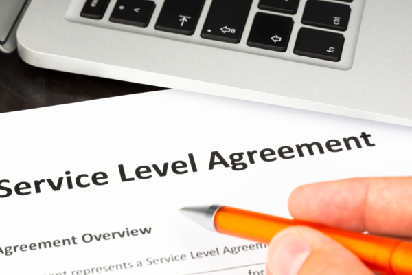 A hand holding a pen over a Service Level Agreement
