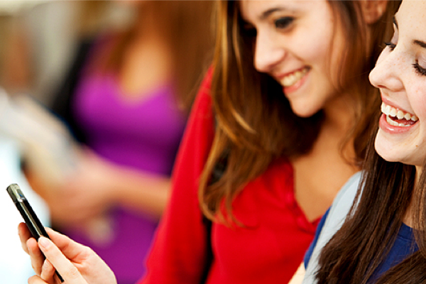 [photo] 2 smiling young women looking at a cellphone