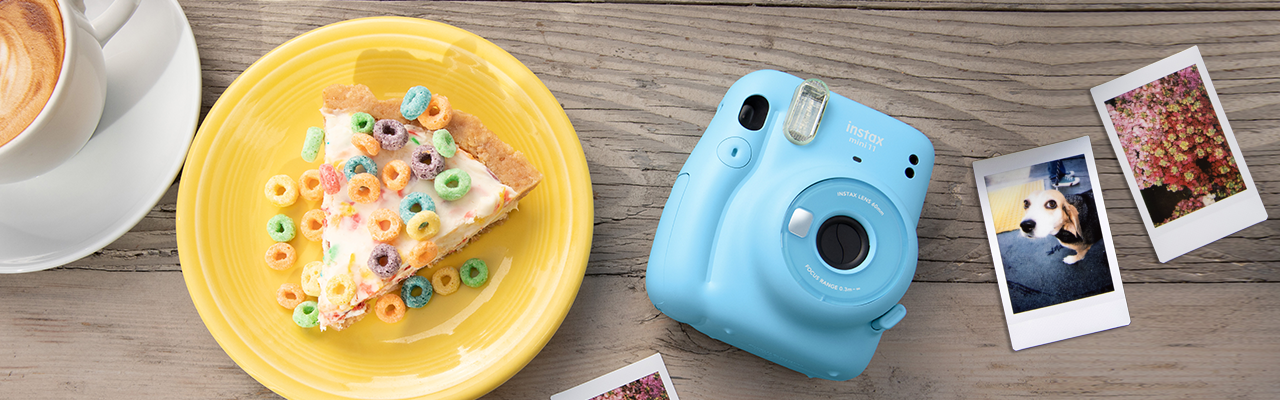 [photo] Fujifilm Instax Mini 11in blue with sample prints and breakfast and a cup of coffee on a wooden table