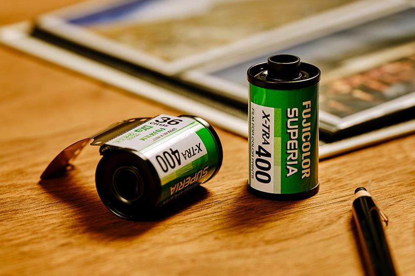 [foto] 2 pellicole Fujicolor Superia X-Tra 400 su un tavolo di legno con arredi