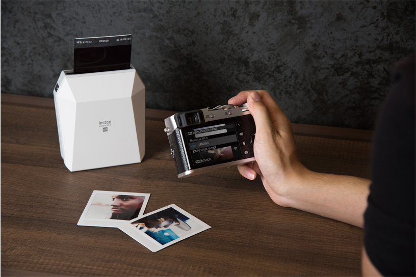 [photo] A lady printing photos from her Instax camera from her Instax SHARE SP-3 in white on a brown table