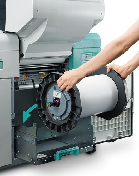 [foto] Brazos de mujer cargando rollo de papel de 180mm en la impresora