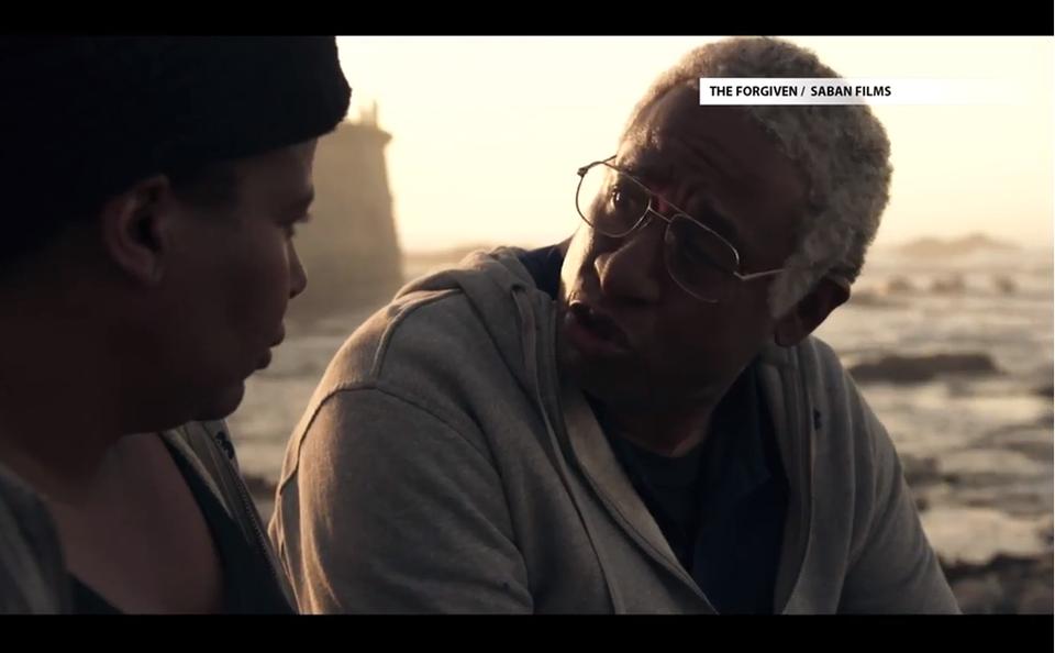 [foto] Una captura de pantalla en primer plano de un hombre mayor hablando con un hombre más joven de la película The Forgiven