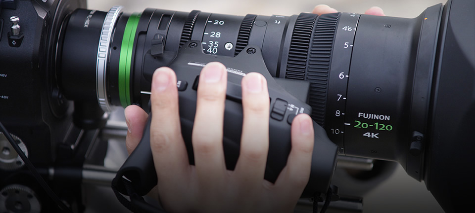 [photo] A cameraman's fingers on zoom buttons attached to an XK Series lens