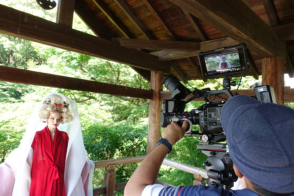 [photo] A camera crew shooting an actress dressed in traditional Japanese attire leaning under a wooden roof