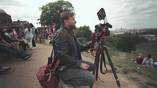 [photo] Man squatting down behind a camera on a tripod
