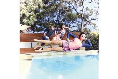 Image of three persons jumping into the pool with white vignette