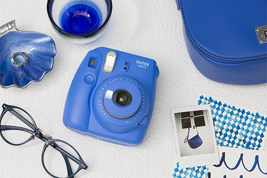 Imagen de una cámara azul Mini 9 sobre la mesa con otros elementos en color azul