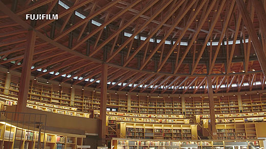 [photo] Immersive circular library with beams of wood jutting across ceiling