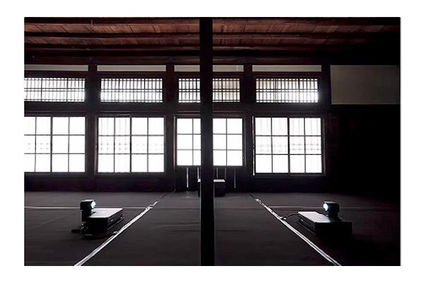 [foto] Una habitación grande vacía con grandes ventanas y dos proyectores en el centro enfrentados