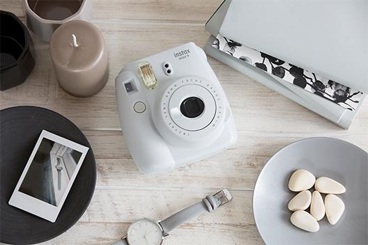 Imagen de una cámara blanco ahumado Mini 9 sobre la mesa con otros elementos