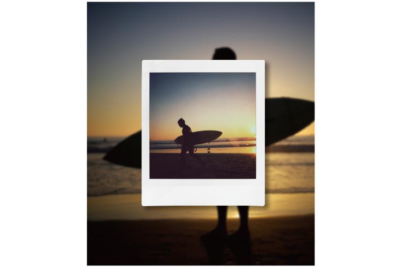 Imagen de una persona con una tabla de surf en la playa con una fotografía INSTAX de una persona con una tabla de surf en la playa en el frente