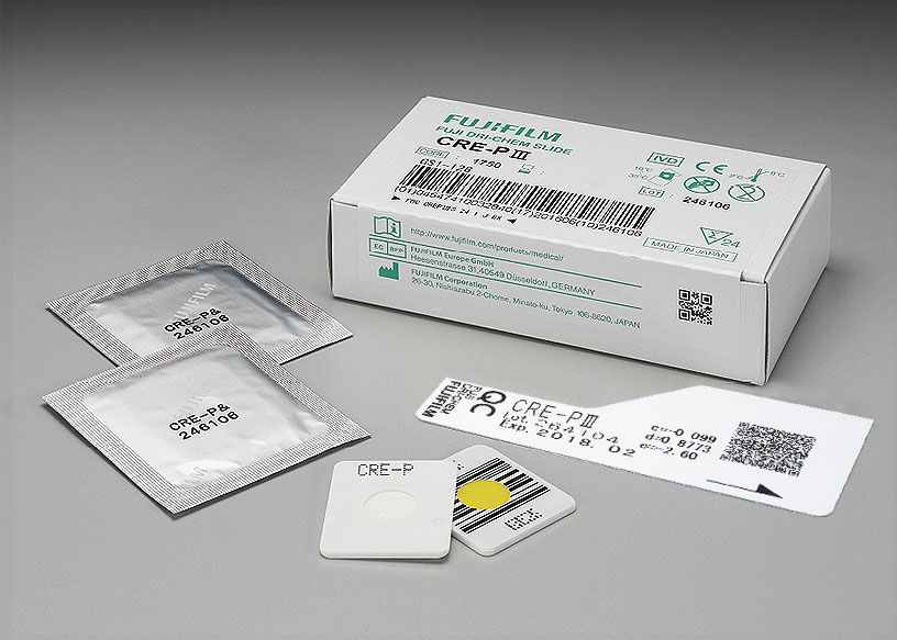 [photo] Box of CRE-PⅢ DRI-CHEM Slides with 2 slides in foil wrapper, 2 slides without packaging (front and back view), and QC card