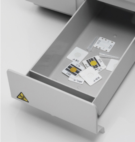 [photo] Disposal box open and pulled out with disposed slides inside tray - box labeled with yellow biohazard sticker in corner